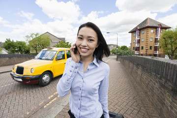 Portrait of smiling businesswoman answering cell phone on sidewalk with taxi in background