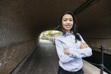 Portrait of confident businesswoman standing arms crossed under bridge