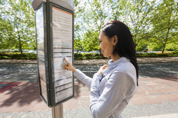 Side view of young businesswoman reading information sign on street