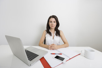 Portrait of confident businesswoman with laptop and binder at desk in office