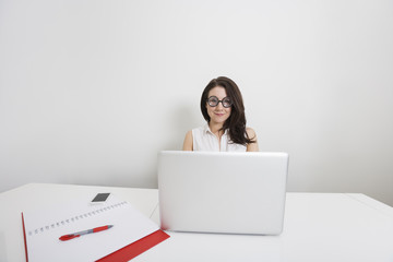 Portrait of young businesswoman in nerd glasses with laptop at desk in office