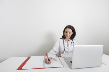 Female doctor writing on binder at desk in clinic