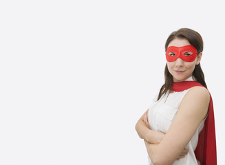 Portrait of confident businesswoman dressed as superhero standing arms crossed in office