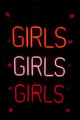 Girls written in neon lights against black background