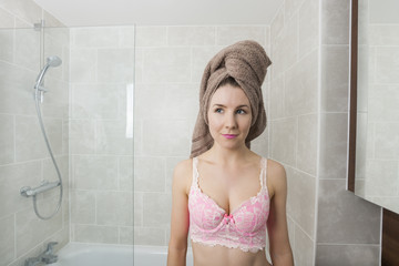 Beautiful woman with hair wrapped in towel at bathroom