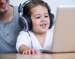 Little girl wearing headphones while looking at laptop with father at table in house