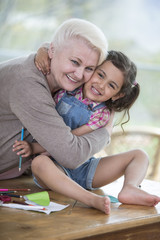 Portrait of senior woman hugging granddaughter sitting on table at home