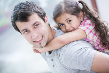 Side view portrait of smiling man piggybacking little daughter at home