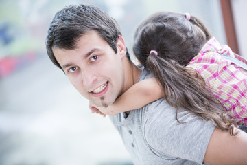 Side view portrait of young man piggybacking little daughter at home