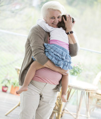 Portrait of loving grandmother carrying granddaughter at home