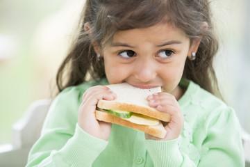 Little girl eating sandwich at home