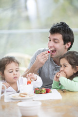 Father and daughters eating strawberries with whipped cream at home
