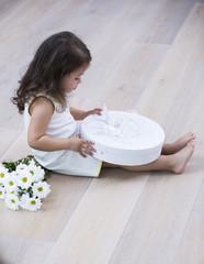 Full length side of little girl opening gift box on floor at home