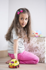 Side view of girl playing with toy car at home