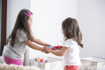 Side view of sisters fighting for toy guitar at home