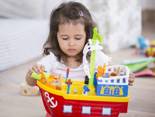 Cute girl playing with toy ship at home