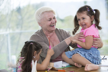 Happy senior woman having quality time with granddaughters at home