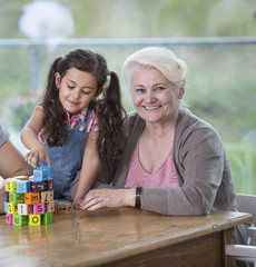 Portrait of smiling senior woman with granddaughter playing with alphabet blocks at home