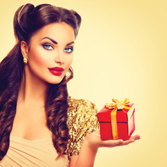 Beauty pin up girl with holiday gift box in her hand