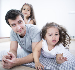 Portrait of father with daughters lying on blanket at home