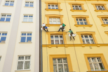 Low angle view of window washers hanging outside building