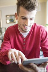 Smiling young man using tablet PC in cafe