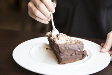 Close-up of woman's hand cutting chocolate pastry