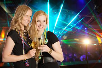 Freundinnen mit Sektgläsern vor Disco-Hintergrund