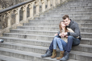 Full length of loving woman kissing man while sitting on steps outdoors
