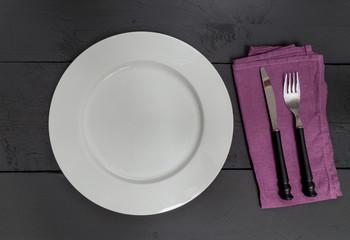 Besteck und Teller auf schwarzen Holzhintergrund