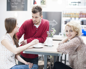 Portrait of smiling woman with friend at cafe table