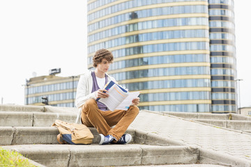 Full length of young male college student reading book against building
