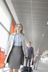 Businesspeople with luggage walking on train platform
