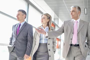 Businesspeople communicating while walking on train platform