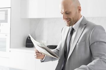 Mid adult businessman reading newspaper in kitchen