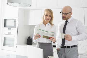 Mid adult business couple reading newspaper while having coffee in kitchen