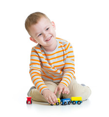 Happy kid boy playing with train toy isolated