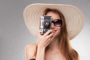 Girl in broad-brimmed hat  and sunglasses with retro camera