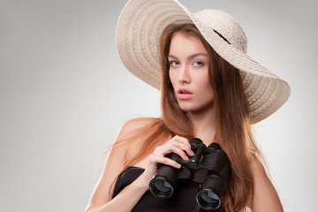 Young woman in hat with binoculars