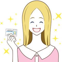 運転免許証を持つ女性 笑顔