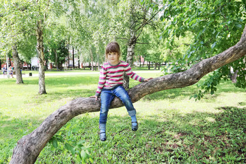 Girl in striped sweater sitting on tree trunk over green grass