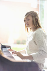 Teenage girl playing piano at home