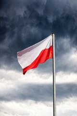 Poland flag on a dark cloudy dramatic sky.
