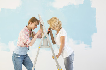 Side view of female friends painting together in new home