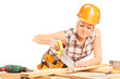 Female carpenter cutting plank with a handsaw