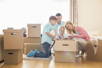 Family unpacking cardboard boxes at new home