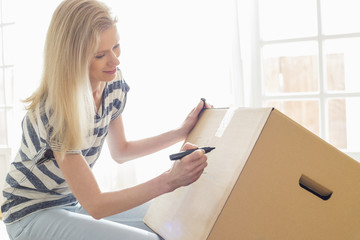Woman labeling moving box at home