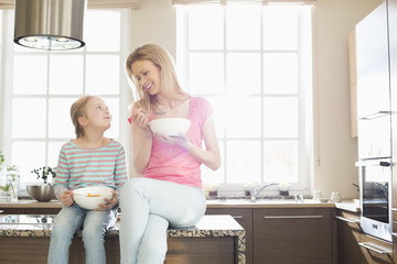 Happy mother and daughter having breakfast in kitchen