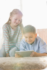 Siblings using digital tablet on floor at home