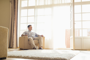 Full length of man relaxing on armchair at home